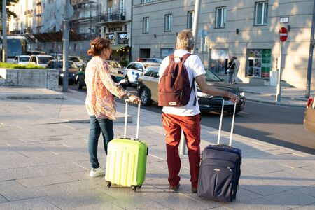 Budapest, Hungary - September 13, 2019: Adult couple travels with suitcases along the street. Love travel and transportation with technology concept.