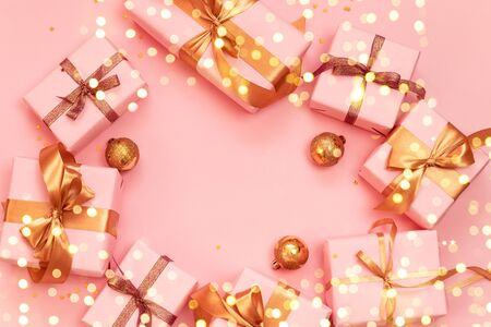 Christmas decorative composition with paper gift box, gold Christmas balls and gold ribbon bow on a pink background. Flat lay, top view for holiday shopping on boxing day