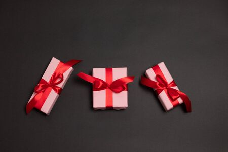 Three surprise gifts wrapped with red ribbon bow on a dark background. Stock Photo