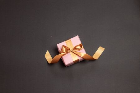 Beautiful surprise gift wrapped in pink paper with a gold ribbon bow on dark background. Stock Photo