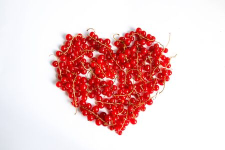 Valentines Day. Love concept of red fresh fresh redcurrant berries in the shape of a heart on a white background. Stock fotó