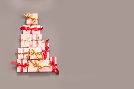 Christmas decorative composition with paper gift box, gold balls, gold ribbon bow and confetti on grey background. Flat lay, top view Stock Photo