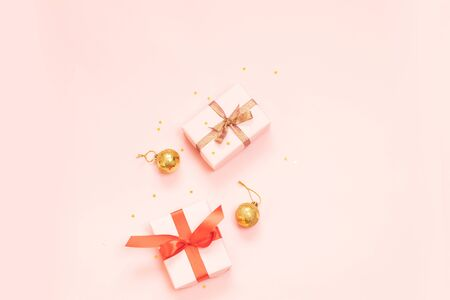 Christmas decorative composition with paper gift box, gold balls and gold ribbon bow on a pink background. Flat lay, top view Stock Photo