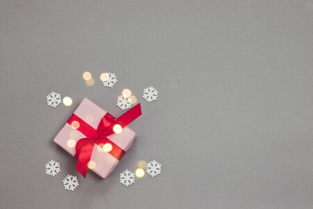 Christmas decorative composition with paper pink present, red bow and confetti on grey background.