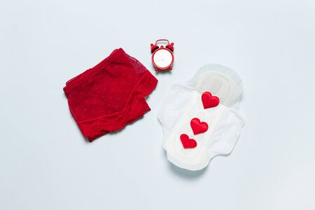 Female lace red panties with medical female slim cotton menstruation pad and clock against critical days on a blue background. Menstruation, protective equipment.