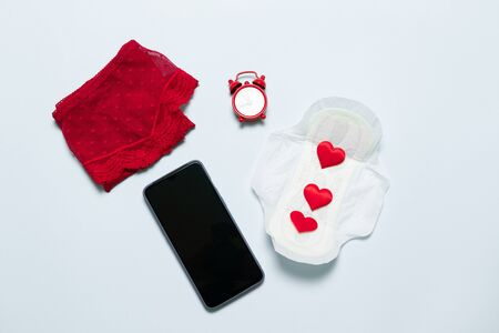Female lace red panties with medical female slim cotton menstruation pad, phone and love shape on a blue background.