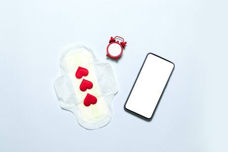Slim cotton menstruation pad with red love shape as blood drops, smartphone template on blue background. Menstruation period concept.