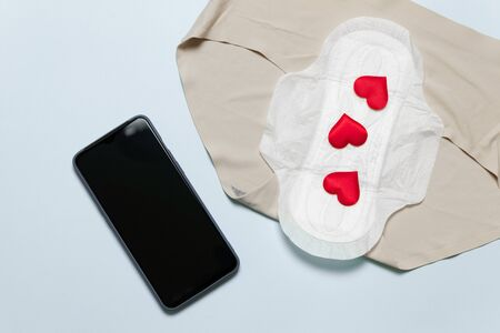 Slim cotton menstruation pad with red love shape as blood drops, smartphone on blue background. Menstruation period concept.