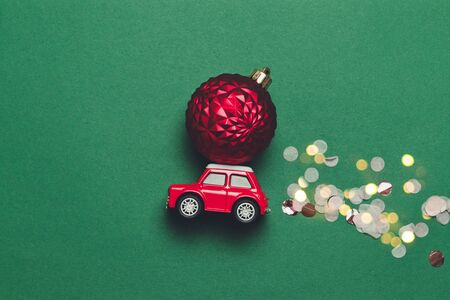 Modern Christmas composition with a red toy car with a Christmas ball on the hood and sparkles candy on a green background with compise. Flat lay, minimal style