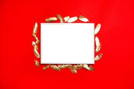 Creative vertical composition of white blank postcard template with gold leaves on red background.