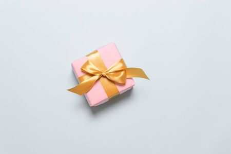 Valentines day, Mothers Day, Fathers Day, Birthday festive background. Surprise gift or box wrapped in paper and satin ribbon on a grey background.