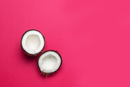 Fresh cracked coconut on pink colored background, minimal flat lay style top view.