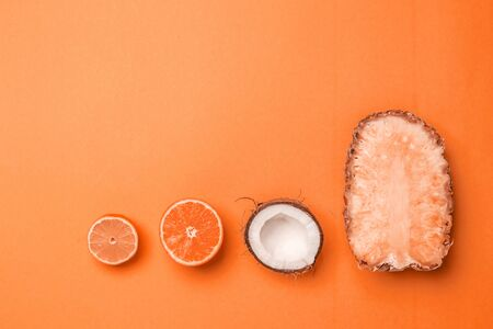 Flat lay summer background with exotic fruits pineapple, orange, lemon, half coconut in orange tint with place for text. Creative minimal postcard 版權商用圖片