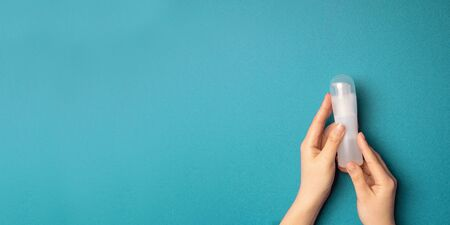 Female hands holding a plastic bottle with a lubricant on a blue background with copyspace. Masturbation concept