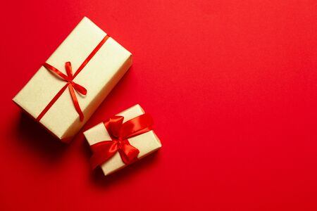 Red minimalistic background with surprise gifts in brown paper and red silk ribbon with copy space. Horizontal composition for banner, poster or greeting card.