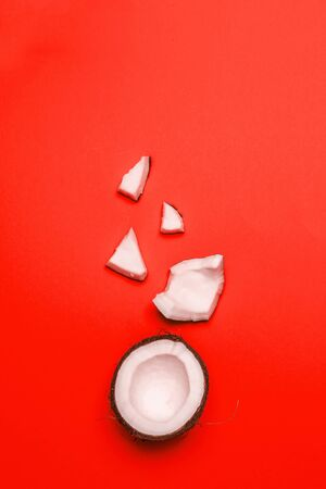 Beautiful half and pieces of coconut lie in a chaotic manner on a red background. Can be used for promo, web, story, article, blog