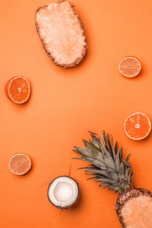 Minimal tinted composition with exotic fruits on an orange background. Summer concept