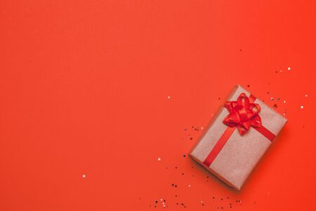 Cute little surprise gift box with red bow decor on a red background. View from above, flat lay 版權商用圖片