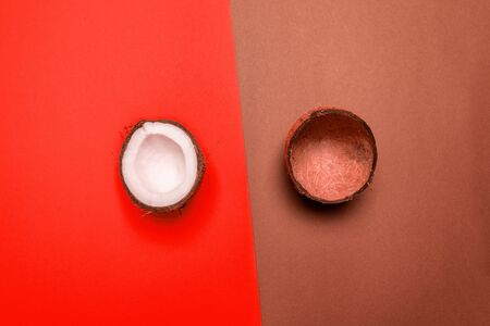 Top view of half coconut on a red background and coconut shell on a brown background. Summer concept 版權商用圖片