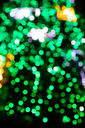 Blurred green fir tree with yellow Christmas lights on background, bokeh effect. Vertical photo