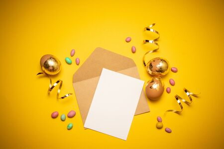 Empty envelope with a blank sheet of paper on a yellow background. Colorful dragee sweets and shiny streamer decor. Layout or template for banner, article, product advertisement. 版權商用圖片