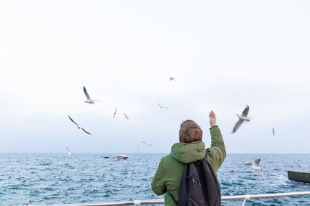Young blonde man with a warm green winter jacket back side feeds bread large white gulls on a pier near the sea. Big blue waves and blue sky. Black backpack