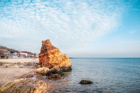 Sharp big red stones near the shore of the Black Sea with blue clouds sky. Amazing seascape