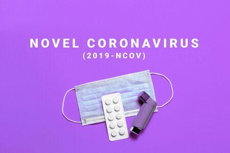 Medical mask, pills, asthma spray with the inscription on a purple background. Vaccine or fight against Coronavirus concept, Novel coronavirus 2019-nCoV, MERS-Cov