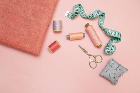 Top view of sewing machine with accessories for sewing, scissors and a measuring tape on pink background Фото со стока