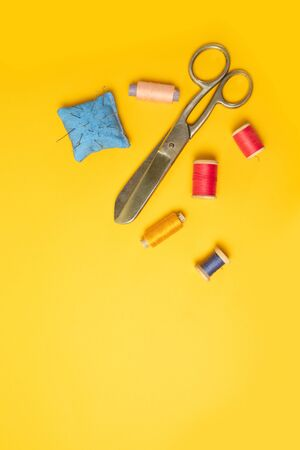 Multi-colored threads pink reels, measuring tape, sewing machine needles on a background. Sewing accessories for needlework, sewing. Place for text. Vertical position