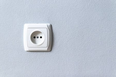 White plastic empty electrical sockets on gray wall with copyspace. Electrical point of power in house Фото со стока