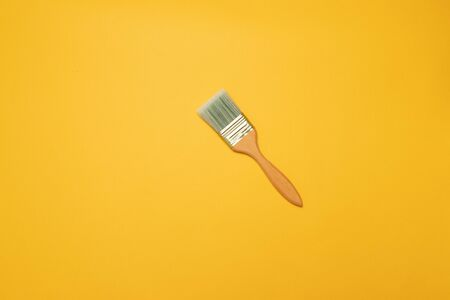 Wooden painters brush on a yellow background, top view, flat lay style