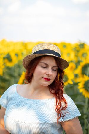 Girl in straw hat and dress in sunflowers. Red lipstick, bright makeup