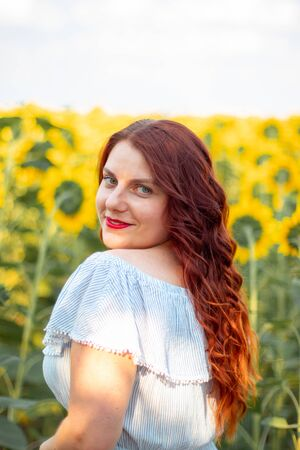 Young red hair Caucasian girl in cotton dress in a field of yellow sunflowers on a sunny day