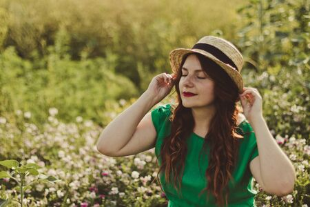 Young curly caucasian girl in a green dress and a straw hat smiles in a flower field on a sunny day. Spring or summer panorama photo