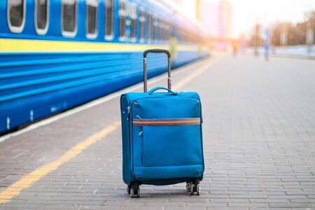 Blue carry on suitcase with wheels and a metal handle stands on the peron of the station. Passenger fast train in the background blurred. Travel concept