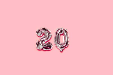 Silver foil balloon number 20 on a pink background. Holiday minimal composition