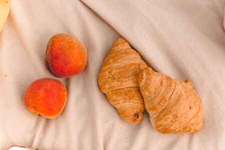 Fresh baked croissants and ripe peaches fruit on a beige plaid. Summer picnic, top view.