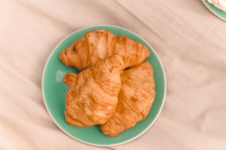 Fresh croissants on a green plate. Summer picnic, top view.