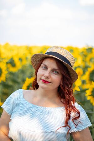 Young red hair Caucasian girl in summer cotton dress and straw hat in a field of yellow sunflowers on a sunny day. Red lipstick, bright makeup