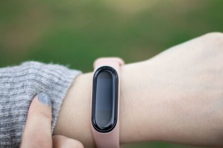 Close up of young sporty woman monitoring his fitness progress with help of smart tracker. Diet, healthy lifestyle.