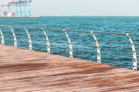 Empty promenade on a sunny day. Metal railings and wooden beams of a terrace along the sea. Langeron city beach on a sunny spring morning. Фото со стока