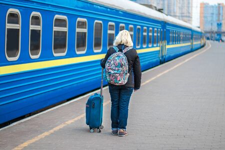 Adult blonde woman in a black jacket goes back to the platform of the train station, waiting for the arrival of the train