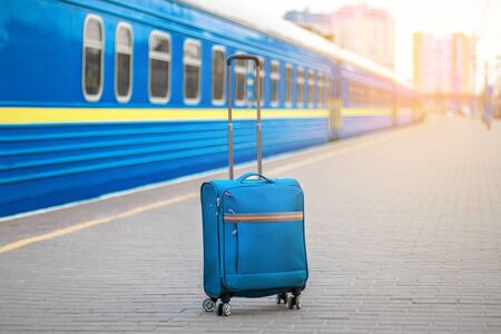 Train station and blue carry-on suitcase with metal handle on the platform. In the background, train cars tend to distance. Empty platform, epidemic, suspension of railway traffic