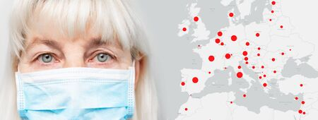 Face of a woman in a medical mask on a grey horizontal background. Covid-19 pandemic epidemic red areas on a global map of the world. Virus protection