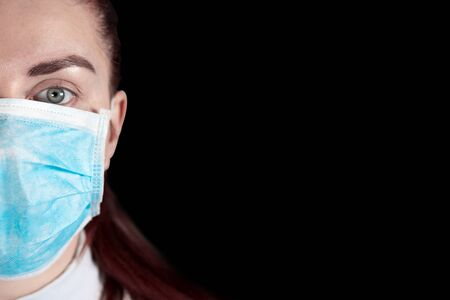 Girl in a medical mask on a black background. Protection against diseases, epidemics and viruses. Coronavirus Covid 19 Фото со стока