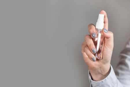 Human hand holds a disinfectant for coronavirus. Spray bottle. Close up individual using cleaning spray