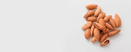 Bunch of inshell almonds with copy space on gray background. Proper nutrition balance