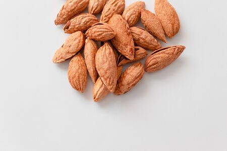 Inshell almonds heap on grey background. High calorie healthy food, proper nutrition and snacks. Wholesome food, proper nutrition and snacks