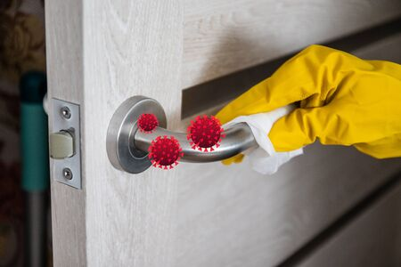 Cleaning lady in rubber latex gloves wipes the metal doorknob with a special disinfectant and a napkin to protect against the virus and germs. Coronavirus, covid 19 Banque d'images